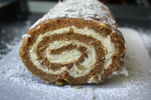 Apple Cake Roll is a moist spiced apple cake rolled in coconut, powdered sugar and pecans and filled with a sweetened cream cheese mixture.