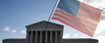 A protester holds up a flag in front of the U.S. Supreme Court (REUTERS/Kevin Lamarque)