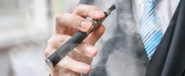 Businessman holds vaporizer and is smoking electronic cigarette. (Credit: Shutterstock/vchal)