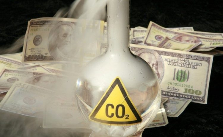 A 500ml beaker filled with CO2 infront of a pile of money, representing the business interest behind the Global Warming scare (Shutterstock.com / mikeledray)