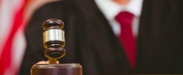 Judge slams a gavel in the court room. (Shutterstock)