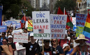 People march protecting the DNC email wikileaks scandal and holding signs in support of former Democratic presidential candidate Bernie Sanders. (PATRICK T. FALLON/AFP/Getty Images)