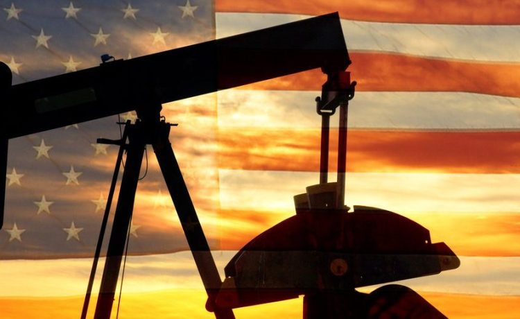 Landscape image of a oil well pumpjack wiith an early morning golden sunrise and American USA red White and Blue Flag background. (Shutterstock/James BO Insogna)