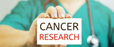 Doctor holding a business card with capital lettering cancer research in hand, (Shutterstock/Have a nice day Photo)