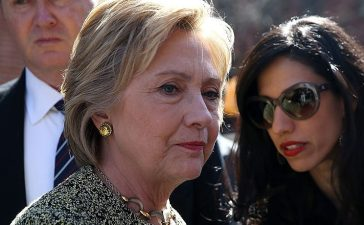 Hillary Clinton (L) talks with aide Huma Abedin (R) before speaking at a neighborhood block party on April 17, 2016 (Getty Images)