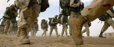 U.S. Marines from the 1st Marine Division return from a six-mile march February 15, 2003 near the Iraqi border in Kuwait. The Marines continue to prepare for a possible military strike against Iraq. (Joe Raedle/Getty Images)