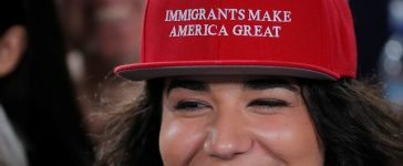 """Audience member Ana Gomez wears a cap reading """"Immigrants Make America Great"""" in the style of hats worn by U.S. Republican presidential candidate Donald Trump at a campaign Voter Registration Rally with U.S. Democratic presidential nominee Hillary Clinton. REUTERS/Brian Snyder - RTX2OEI6"""
