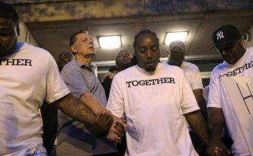 Father Michael Pfleger (2nd L) prays at Saint Sabina Church before taking part in a weekly night-time peace march through the streets of a South Side neighborhood in Chicago, Illinois, September 16, 2016. REUTERS/Jim Young