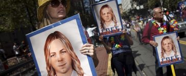 People hold signs calling for the release of imprisoned wikileaks whistleblower Chelsea Manning while marching in a gay pride parade in San Francisco, California