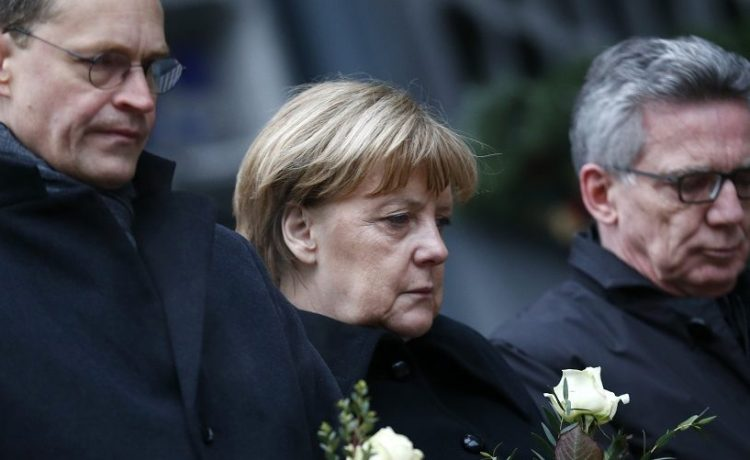 Berlin mayor Mueller, German Chancellor Merkel and German interior minister de Maiziere stand in silence at the Christmas market in Berlin