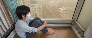 Mask-wearing Chinese boy looking outside the window on extremely polluted day (Shutterstock/Hung Chung Chih)