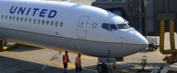 FILE PHOTO - Two ground crew members walk past a United Airlines airplane as it sits at a gate at Newark Liberty International Airport in Newark, New Jersey, June 18, 2011. REUTERS/Gary Hershorn/File Photo