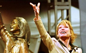 """Mary Tyler Moore tosses her tam skyward replicating the action shown during the opening credits of the 1970's sitcom, """"The Mary Tyler Moore Show,"""" in downtown Minneapolis, May 8, 2002. (Photo credit: REUTERS/ Eric Miller)"""