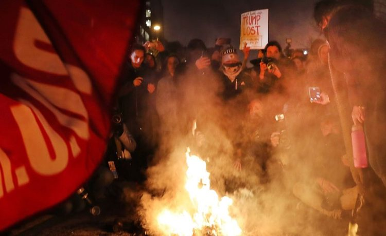 WASHINGTON, DC - JANUARY 20: A protester sits by a fire in the street as police and demonstrators clash in downtown Washington following the inauguration of President Donald Trump on January 20, 2017 in Washington, DC. Washington and the entire world have watched the transfer of the United States presidency from Barack Obama to Donald Trump, the 45th president. (Photo by Spencer Platt/Getty Images)