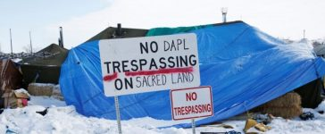 """A modified """"No Trespassing"""" sign is seen in the opposition camp against the Dakota Access oil pipeline (DAPL) near Cannon Ball, North Dakota, U.S., February 8, 2017. REUTERS/Terray Sylvester"""