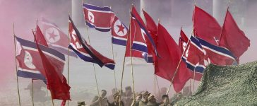 South Korean Army soldiers, acting as North Korean soldiers, hold North Korea's flags as they take part in a re-enactment of the Nakdonggang Battle, September 3, 2010. REUTERS/Jo Yong-Hak