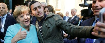 Syrian refugee Anas Modaman takes a selfie with German Chancellor Angela Merkel outside a refugee camp near the Federal Office for Migration and Refugees after registration at Berlin's Spandau district, Germany September 10, 2015. A German court will on February 6, 2017 hold its first hearing in the case of a Syrian refugee who is suing Facebook after the social networking site declined to remove all posts linking him to crimes and militant attacks. REUTERS/Fabrizio Bensch
