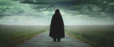 Grim reaper walking on a dark desolate road. [Shutterstock - Captblack76]