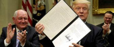 U.S. President Donald Trump shows a signed executive order next to Secretary of Agriculture Sonny Perdue during a roundtable discussion with farmers at the White House in Washington, U.S. April 25, 2017. REUTERS/Yuri Gripas