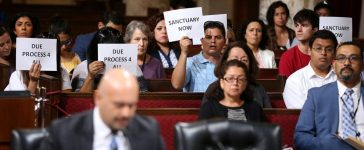 Immigrant supporters protest duirng the Los Angeles City Council ad hoc committee on immigration meeting to discuss the city's response to threats by the Trump administration to cut funding from Los Angeles and other jurisdictions which federal officials say are providing sanctuary to illegal immigrants arrested for crimes, in Los Angeles, California, U.S., March 30, 2017. REUTERS/Lucy Nicholson