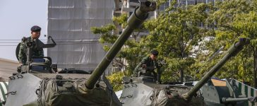 Thai soldiers sit on top of tanks at the Army base in central Bangkok January 10, 2014. The Royal Thai Army moved military hardware into Bangkok ahead of an exhibition for national Children's Day this Saturday, according to the military. REUTERS/Athit Perawongmetha
