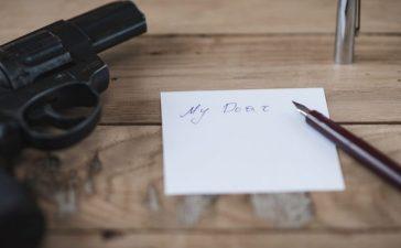 A gun and a suicidal note. [Shutterstock - Roman Demkiv]
