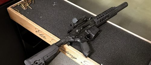 A suppressed SigSauer rifle rests on a bench at Elite Shooting Sports in Manassas, Va. Bobby Cox, director of government strategy at SigSauer, says the company makes suppressors for all its commercially available firearms. (PHOTO: Will Racke/TheDCNF)
