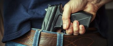 A man reaches for a concealed pistol. (Shutterstock/Maksym Dykha)