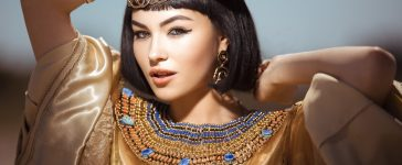 Photo of gorgeous woman with Cleopatra makeup, closeup portrait of beautiful female with stylish haircut agaist, young lady wearing fashionable golden necklace and holding magik ball outdoor, beauty (Shutterstock/Dmytro Buianskyi)