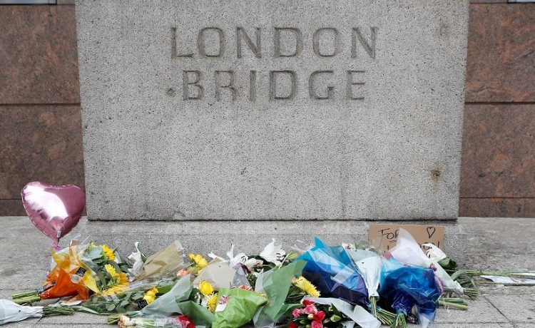 A woman passes flowers left on the south side of London Bridge near Borough Market after an attack left 7 people dead and dozens of injured in London