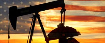 Landscape image of a oil well pumpjack wiith an early morning golden sunrise and American USA red White and Blue Flag background. (Shutterstock/ James BO Insogna)