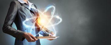 Atom molecule in hands . Mixed media (Shutterstock/Sergey Nivens)