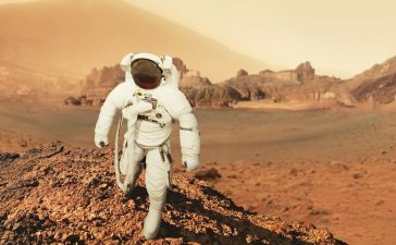 Astronaut man walks in the desert with mountains in Mars. Journey to the red planet. Landscape of the red planet Mars (Shutterstock/Alones)