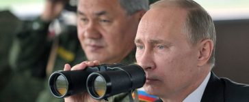 Russian President Vladimir Putin (R) and Defence minister Sergei Shoigu (L) inspect military exercises in the Pacific Ocean near the Sakhalin island on July 16, 2013. (Photo: ALEXEI NIKOLSKY/AFP/Getty Images)
