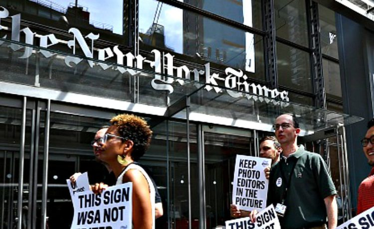 NEW YORK, USA - JUNE 29 : New York Times (NYT) employees hold banners during a temporary strike against downsizing and dismissal plans of the NYT management outside of New York Times building in New York, United States on June 29, 2017. (Photo by Volkan Furuncu/Anadolu Agency/Getty Images) Restrictions