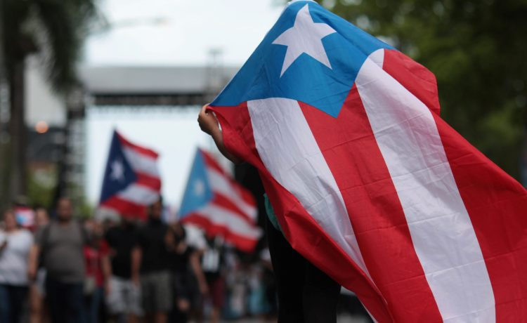 A person carries a Puerto Rican national flag during a protest against the government's austerity measures as Puerto Rico faces a deadline on Monday to restructure its $70 billion debt load or open itself up to lawsuits from creditors, in San Juan, Puerto Rico May 1, 2017. REUTERS/Alvin Baez - RTS14QAQ