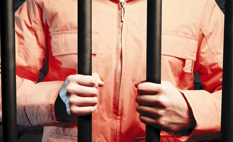 An inmate stands behind bars. (Shutterstock/Fer Gregory)