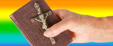 Old hand (woman) holding a very old bible, isolated on white, rainbow flag (MyImages - Micha/shutterstock_135908630)