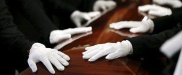 Pallbearers rest their hands on the casket of San Bernardino shooting victim Tin Nguyen during her funeral at Saint Barbara's Catholic Church in Santa Ana, California, December 12, 2015. REUTERS/Patrick T. Fallon