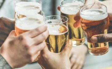 Shutterstock/ Multiracial group of friends enjoying a beer - Young people hands toasting and cheering aperitif beers half pint - Friendship and youth concept - Warm vintage raw filter - Focus on bottom hand Shutterstock/ DisobeyArt