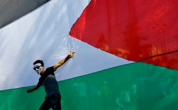 A Palestinian youth poses in front of his national flag during celebrations in Gaza City after rival Palestinian factions Hamas and Fatah reached an agreement on ending a decade-long split following talks mediated by Egypt on October 12, 2017. (Photo: MOHAMMED ABED/AFP/Getty Images)