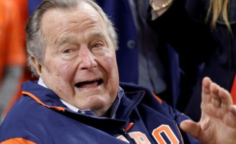 Former U.S. President George H.W. Bush waves from the field in Houston
