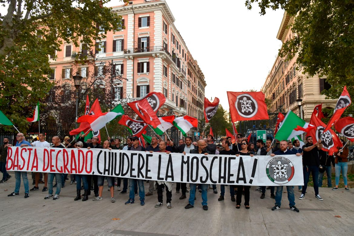 "Supporters of Italian far-right movement CasaPound march behind a banner reading ""Enough deterioration, Close the Mosque"" during a protest against a mosque situated in Via San Vito on October 4, 2017 in the Esquilino district of Rome. / AFP PHOTO / Andreas SOLARO (Photo credit should read ANDREAS SOLARO/AFP/Getty Images)"