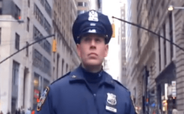 An NYPD police officer stands ready for action (Photo Credit: YouTube/NYPD)