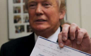 Then presidential candidate Donald J. Trump holds a check in Concord, New Hampshire November 4, 2015. REUTERS/Brian Snyder