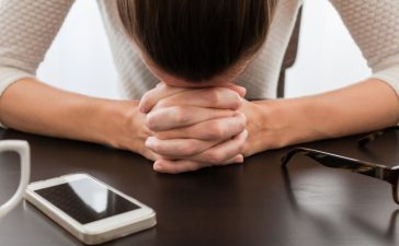 Woman stressed out because of her smartphone. [Shutterstock - KieferPix]