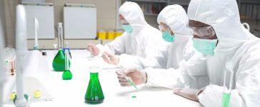 Chemists testing green liquid in petri dishes in the lab. [Shutterstock - wavebreakmedia]