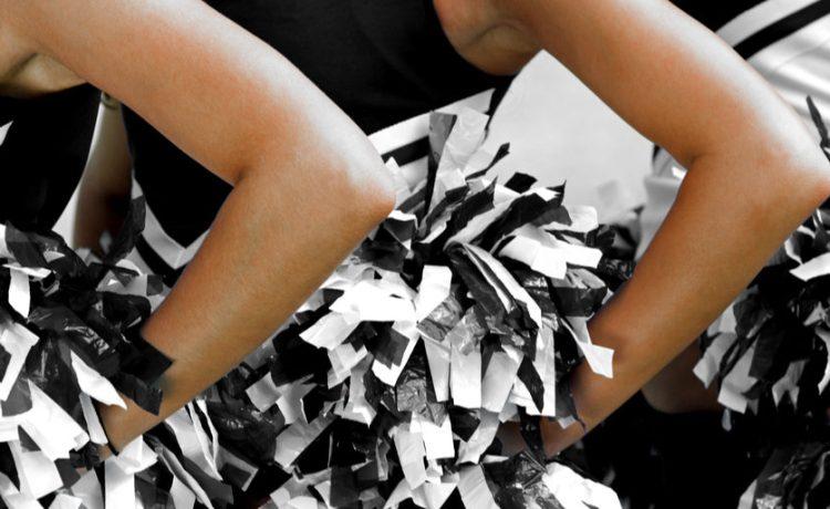 Cheerleaders in Uniform Holding Pom-Poms Shutterstock/ sirtravelalot