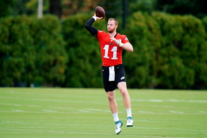 Quarterback Carson Wentz throwing a football during practice.