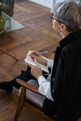 woman in black blazer holding white tablet computer